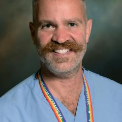 photo of a person with short hair and a mustache wearing a light blue shirt and a rainbow lanyard
