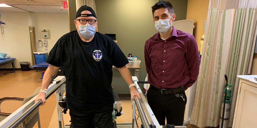 Two men standing in rehab room