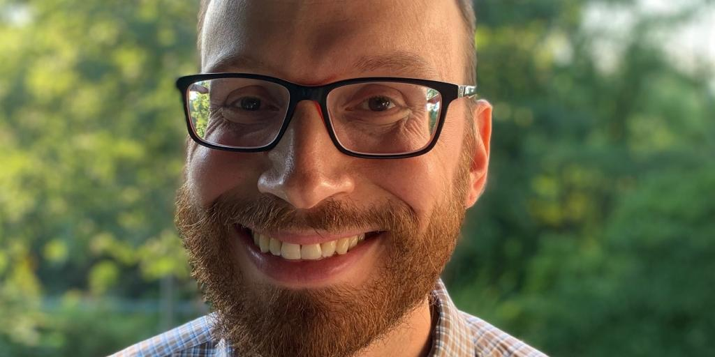 Smiling man in glasses.