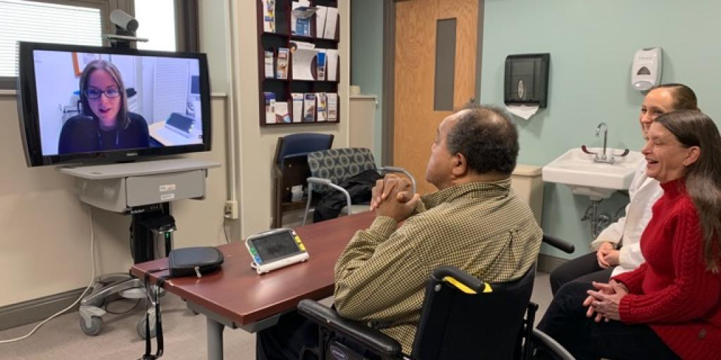 Three people sitting in front of a tv screen talking with someone on the screen.