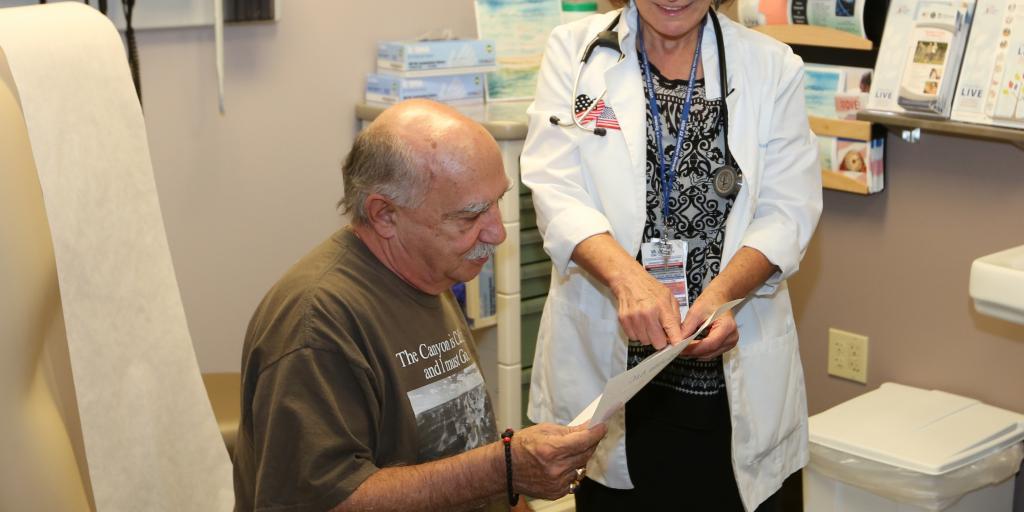 VA female provider discussing health care outcomes with male Veteran.