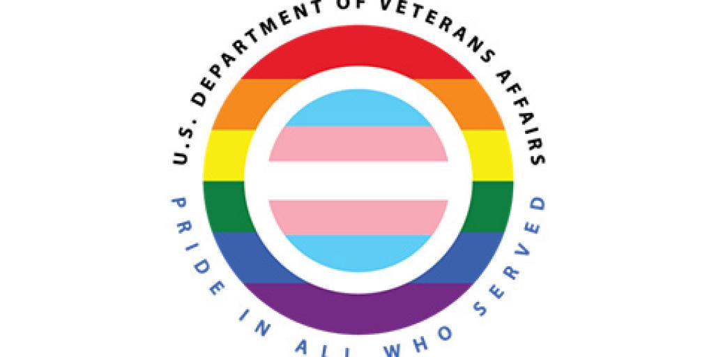 A circle shaped logo. The outer circle is the Lesbian, Gay, Bisexual, and Transgender (LGBT) rainbow flag colors with an inner circle separated by a white band of the transgender flag colors.