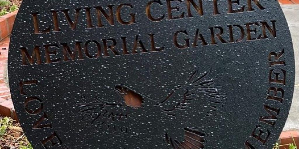 """Charles George VA Medical Center Community Living Center has placed a new sundial shaped sign in its Memorial Garden. Inscribed on the sign are the words """"Loved, Served, Remember""""."""