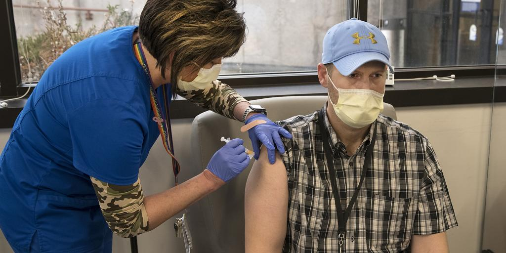 A Veteran receives a COVID-19 vaccination from a VA health care worker