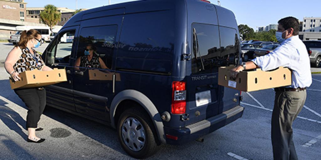 Charleston VAMC Director Scott Isaacks and High Reliability Program Manager Kathleen Gillard load boxes of fresh produce into a Veteran's van. Photo by James Arrowood.
