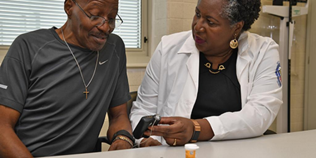 Diabetes Educator Cheryl Pratt instructs Veteran Dewayne Patterson how to use of his insulin pump. Photo by James Arrowood.