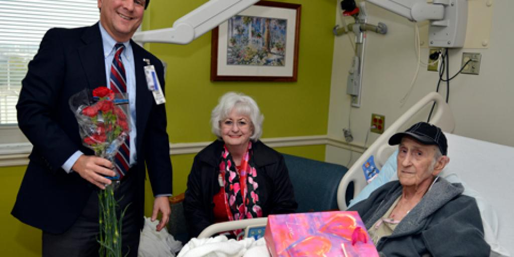 Charleston VAMC Director and CEO Scott Isaacks visits Veteran Michael Scarbourgh and his wife to deliver carnations and well wishes during National Salute to Veteran Patients Week.