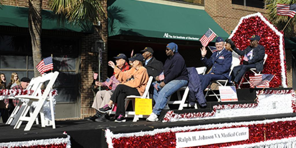 Helen Richards, sister of PFC Ralph H. Johnson, rides on the top tier of the Charleston VAMC Veterans Day Parade Float in the 2017 parade in downtown Charleston.