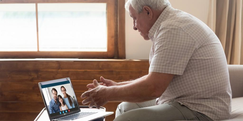 Happy elderly man holding video call with family on laptop