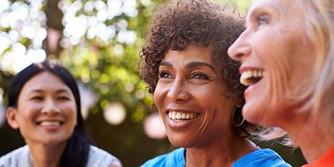 Photo of three middle aged women, multicultural, laughing together