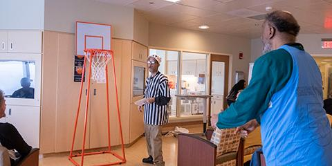 A Veteran shoots a small paper basketball towards a hoop while a referee watches