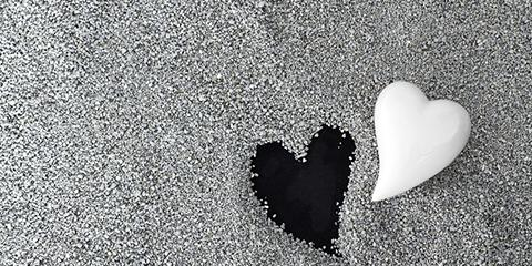 Photo of a white heart and a placeholder in the sand in the shape of a heart