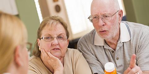 Pharmacist explaining prescription medicine to attentive senior couple