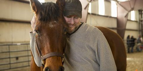 Retired Army National Guard warrant officer Barton Jeffs embraces his horse, Rebel.