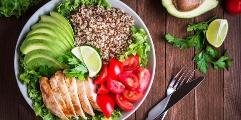 Healthy salad bowl with quinoa, tomatoes, chicken, avocado, lime, and mixed greens