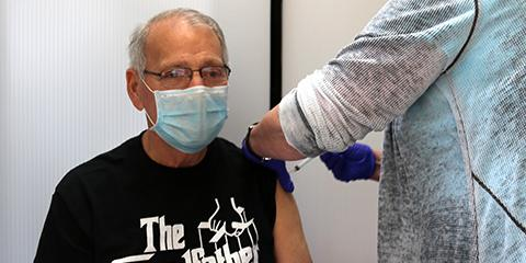 Gary Giorno, a Vietnam era Veteran in a black t-shirt and glasses looks straight ahead as he receives his second dose of the Moderna COVID-19 vaccine.