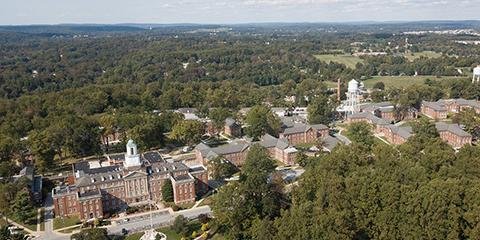 An aerial view of the medical center taken by a drone from the south. From this angle building one is clearly visible while many more buildings are partially visible behind the cover of green trees and vegetation on the 140 acre campus.