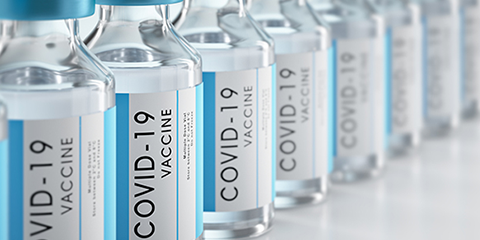Vials of the Johnson and Johnson COVID-19 vaccination lined up and receding from left to right.