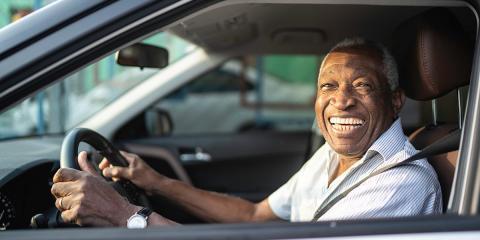 Man smiling inside car.