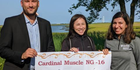 Dr. Huang with two colleagues holding up a banner that reads Cardinal muscle NG-16