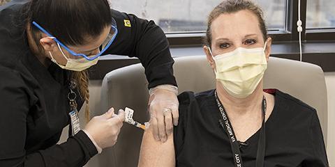 A VA nurse gets a COVID-19 vaccine