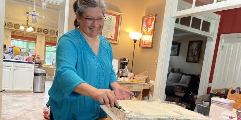 Jeanette Watson adds icing to the cake. She is preparing two cakes with different flavors and a few dozen cupcakes for a VA employee retirement.