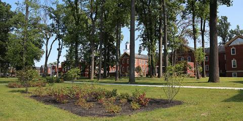 Image of the grounds and landscape at Coatesville VAMC. A brick building is in the background, multiple trees growing and a garden in the front center.