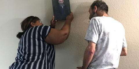 Charleston VAMC employee Desralei Jackson helps install a portrait photo with Douglas Barker on the wall of his new apartment.
