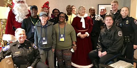 Santa, Mrs. Claus and the City of Charleston Police Department stand with Fisher House families during a special donation for Veterans.