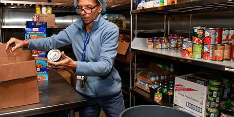 Margaret Bradbury, Chief of Nutrition & Food Service inspecting canned food items for the Ralph H. Johnson VA Medical Center Veteran Food Pantry.