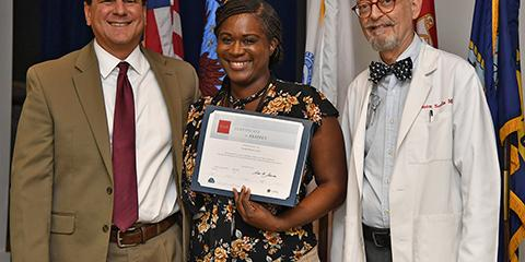 Charleston VAMC Director and CEO Scott Isaacks (left) presents an ICARE award to Tamika Blount-Currie (center) along with Deputy Chief of Staff Dr. Simon Scalia (right) at the monthly employee awards ceremony, one of the new initiatives at Charleston VAMC to recognize staff for going above and beyond to serve Veterans. Photo by James Arrowood.