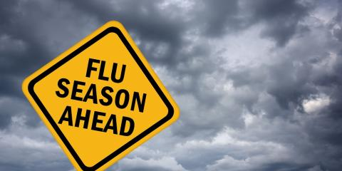 Traffic sign that reads Flu season ahead with dark clouds in the background