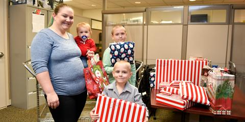 Laken Johnson, a dental technician with the Ralph H. Johnson VA Medical Center Dental Clinic, and her sons Carter, 10, Korbin, 6, and Logan, 1, donate gifts to the Voluntary Service Angel Tree program.