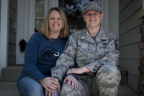 A smiling military couple sitting in front of a house
