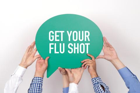 Hands holding up a sign that says Get your flu shot