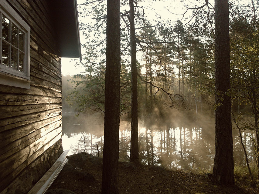 Cabin on a lake with morning mist rising above the lake