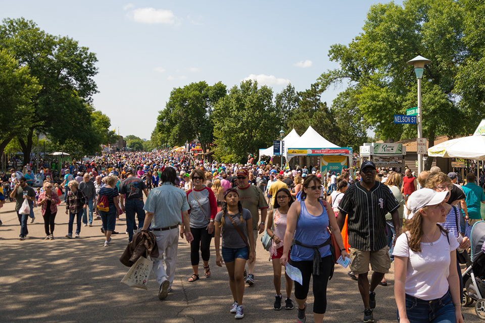 Crowd of people walking at the Minnesota State Fair with the Minnesota Lottery ticket booth in the background