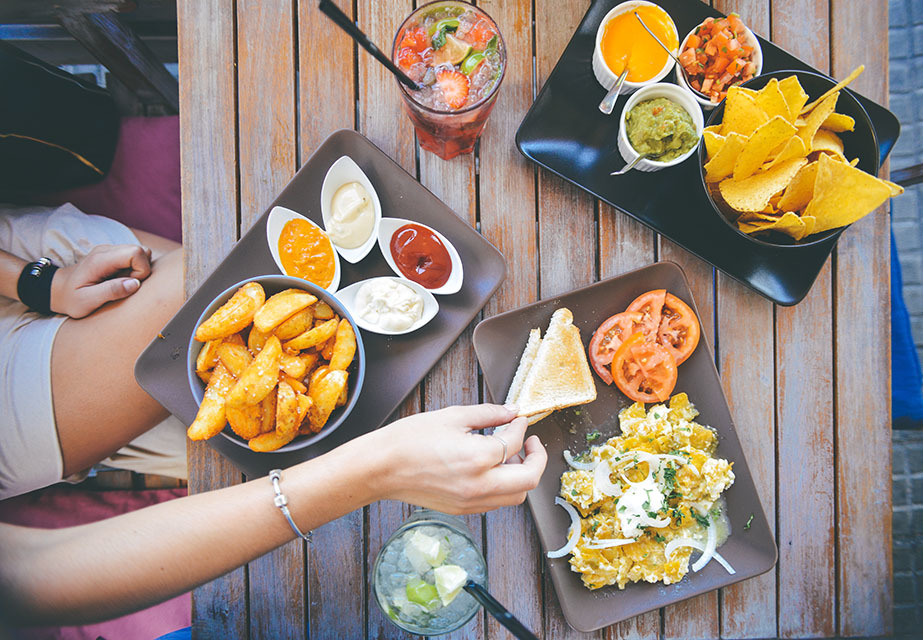 Array of appetizers and drinks with person eating