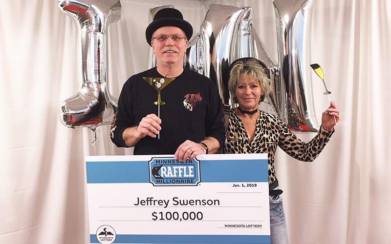 Jeffrey and Debbie Swenson holding their one hundred thousand dollar check.