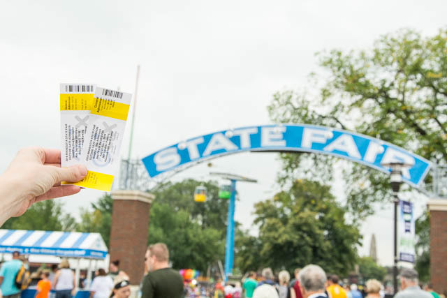 Two tickets held up in front of the State Fair arch
