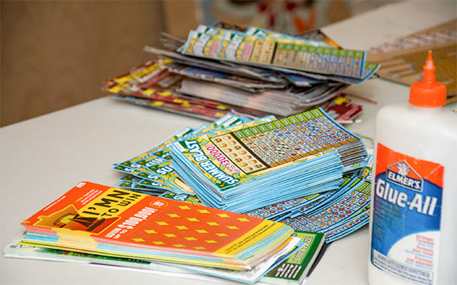 Minnesota Lottery scratch tickets piled between craft supplies.