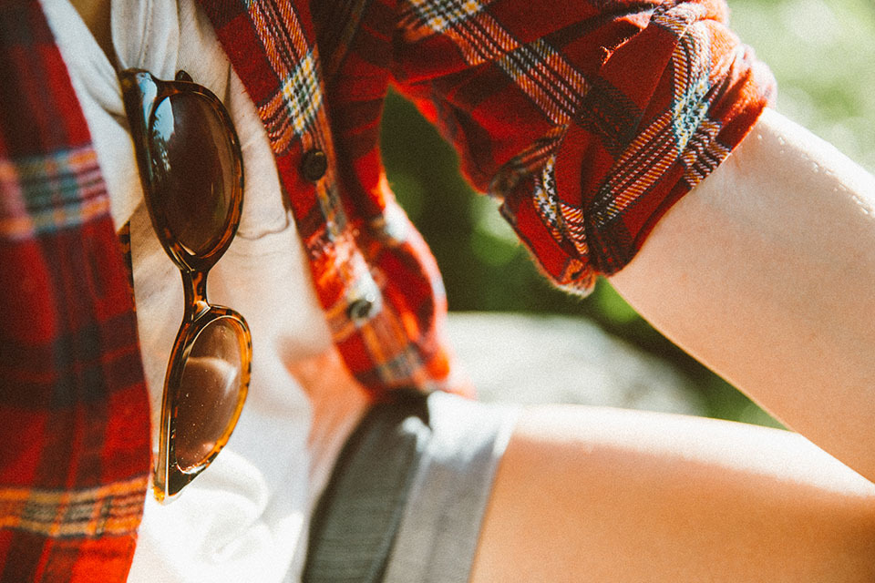 Close-up of sunglasses hooked onto shirt with a flannel shirt over it